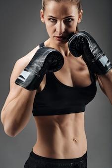 野心的な女性がボクシンググローブでポーズ