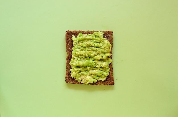 パステルグリーンの背景にアボカドのトースト。茶色いパンのスライスとアボカドペースト。上面図。テキスト用の空き容量。最小限の食品のコンセプト