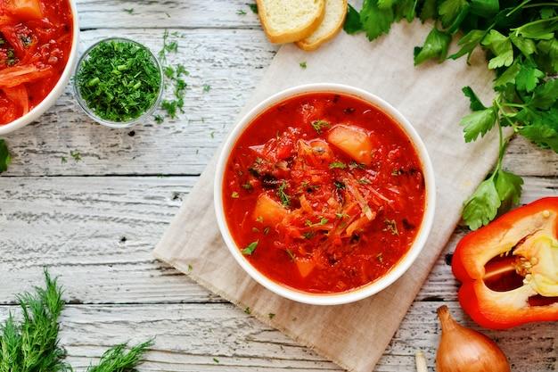 赤いトマトのスープ。ウクライナ語とロシア語のボルシチ。白い木製のテーブルに白いボウルのボルシチ。