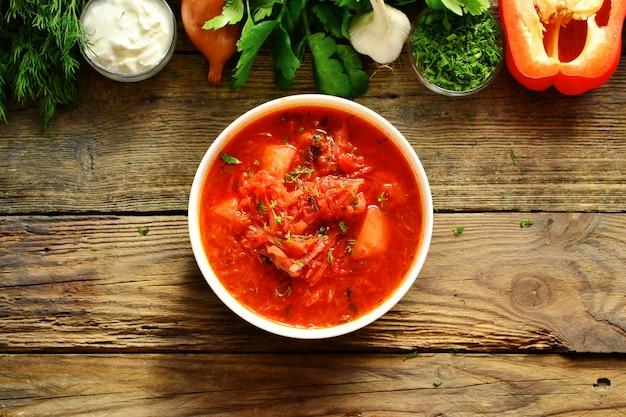 ウクライナ料理とロシア料理、赤いボルシチ。トマトスープ。トマト、ピーマン、パセリ、タマネギ、ジャガイモ、ニンジン、キャベツ、ビートから作られた野菜のボルシチ。上面図