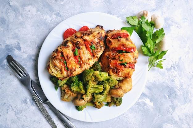 Жареное куриное филе. брокколи и цветная капуста. запеченная куриная грудка. курица и помидор. еда в белой тарелке на светлом столе