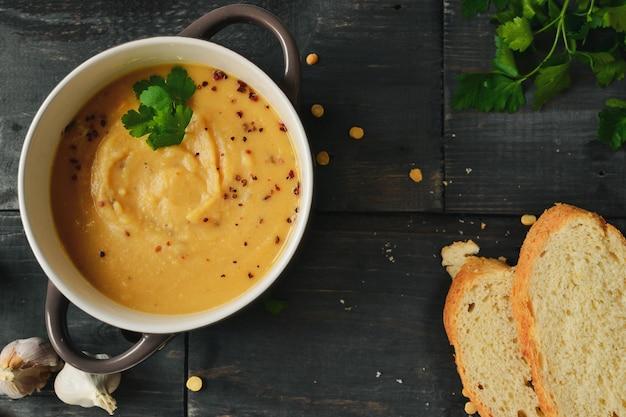 Гороховый суп в миску на деревянном столе. гороховое пюре и каша. вид сверху