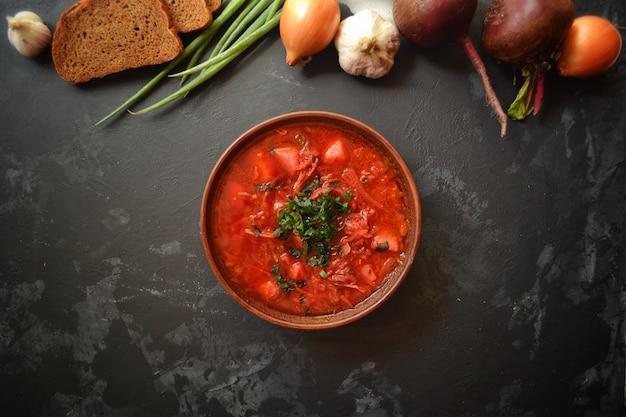 ウクライナ料理とロシア料理。黒い表面に赤いボルシチ。ボルシチと野菜とトマト。
