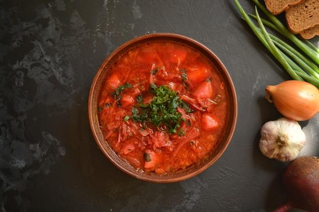 ウクライナ料理とロシア料理。黒い表面に赤いボルシチ。ボルシチと野菜とトマト。ビート、玉ねぎ、パン、トマト、キャベツ、ニンニク。