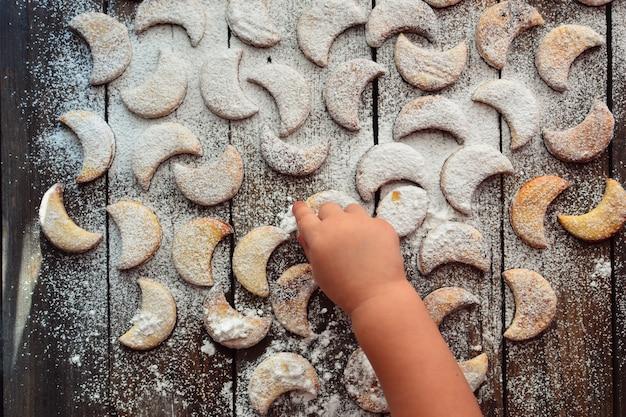 Рождественское печенье в форме луны. ребенок окропляет печенье сахарной пудрой. ребенок и печенье. руки ребенка в сахарной пудре и муке. девушка готовит.