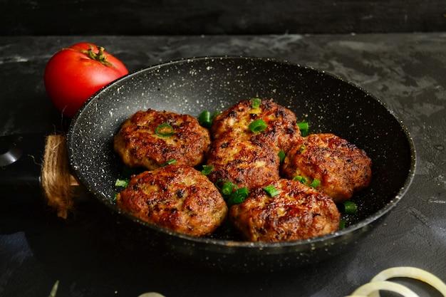 ミートカツ。黒いコンクリートテーブルの上のフライパンでミートボール。おいしいおいしい食べ物。