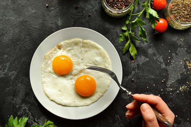 Женщина ест яичницу на завтрак, держит вилку. яичница в тарелке. вид сверху