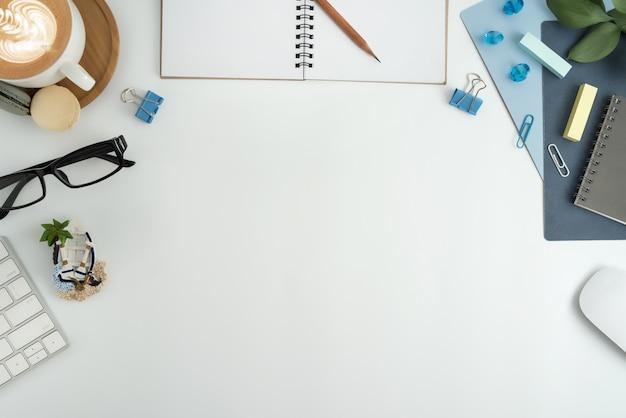 フラットレイ、空白のノートブック、キーボード、事務用品を備えたトップビューのオフィスワークスペース。