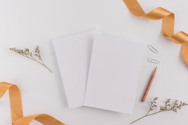 トップビュー、フラットレイ、結婚式招待状、封筒、白い背景のカード用紙。