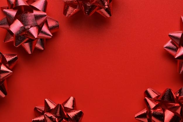 フラットレイ、赤い装飾的なクリスマスのギフトの弓のトップビュー最小構成の背景。