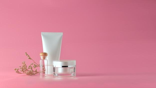 ピンクの背景に化粧品のセットです。ブランディングモックアップ用の化粧品の白紙のラベル。