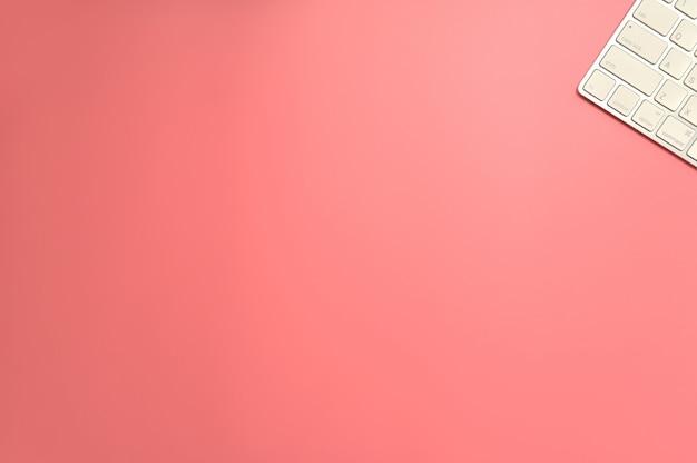 フラット横たわっていた、トップビューオフィステーブルデスク。ピンクの背景のキーボードとワークスペース。