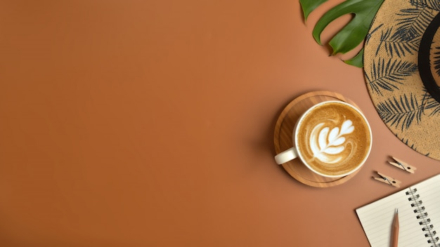 Плоская планировка, вид сверху рабочей области с очки, ноутбук, шляпа, карандаш, зеленые листья, обувь и чашка кофе на коричневом фоне.