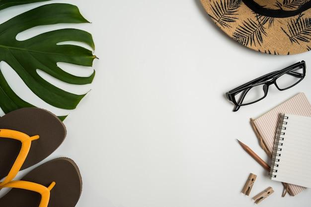 メガネ、ノート、帽子、鉛筆、緑の葉、靴、白い背景の上のコーヒーカップとフラットレイアウト、平面図のワークスペース。