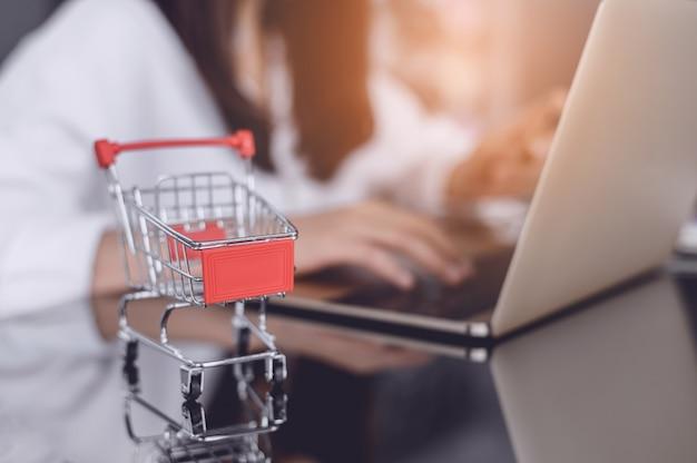 タブレット画面のトロリー。オンラインショッピングに関するアイデア、女の子は電話を使用してインターネット経由で売り手から商品を直接購入します。オンラインショッピング中毒のコンセプト