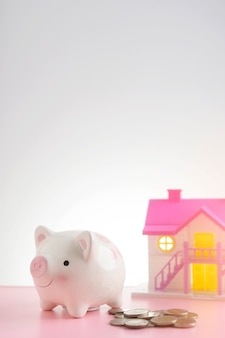 甘い家の背景を持つピンクのテーブルの上の貯金箱の周りのコイン。家や家の節約の概念を購入するために節約