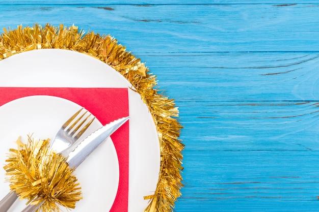 Нож и вилка в белой тарелке на красной салфетке украшены рождественской мишурой