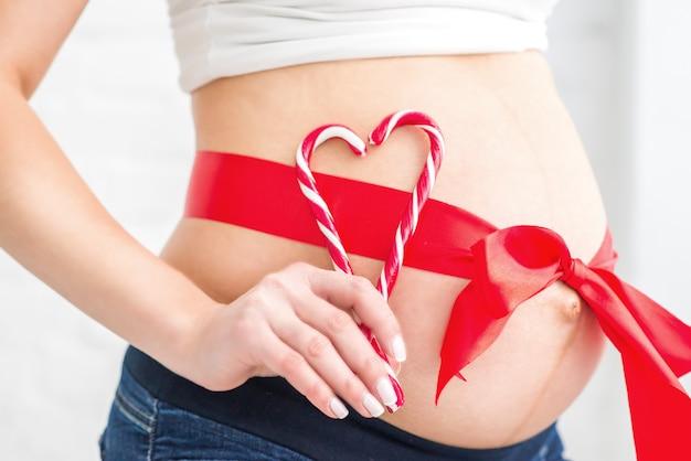 Беременный живот с красным сердцем