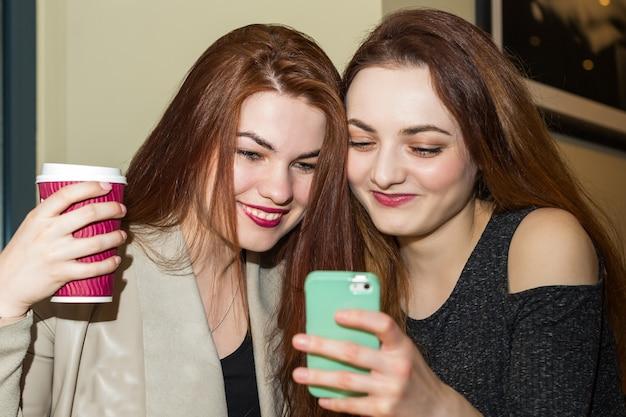Девушка показывает мобильный телефон другу