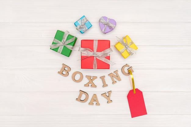 Над подарочными коробками перевязана лента со словами день бокса и красной биркой на белом фоне дерева