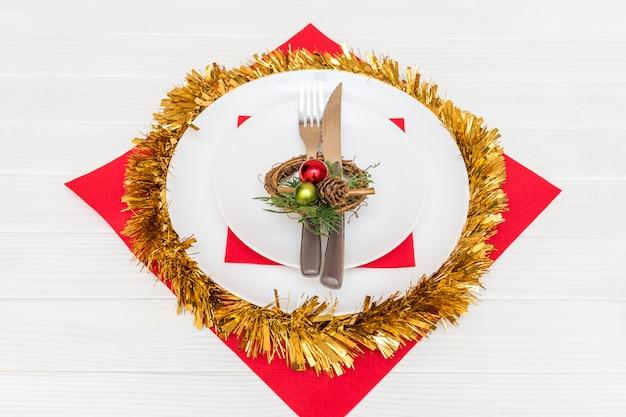 Нож и вилка в белой тарелке на красной салфетке украшены рождественским венком на белом столе