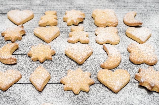 木製のテーブルに砂糖粉でクリスマスの異なる形のクッキー