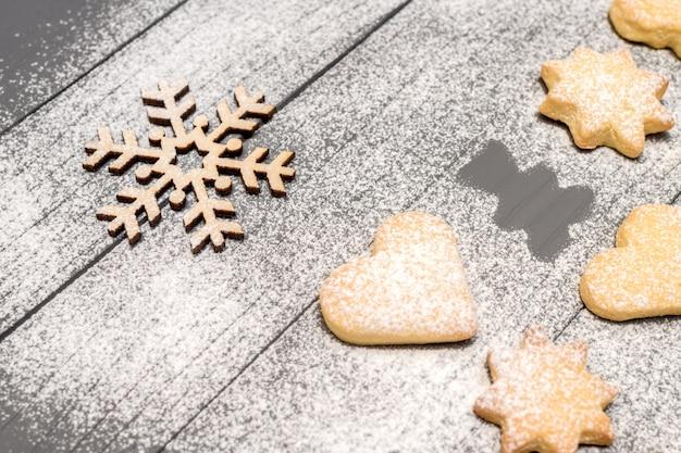 クリスマスの異なる形状のクッキー、シュガーパウダー、木製のテーブルに木製のスノーフレーク