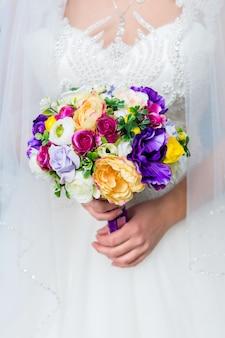 花嫁の手の中のウェディングブーケ