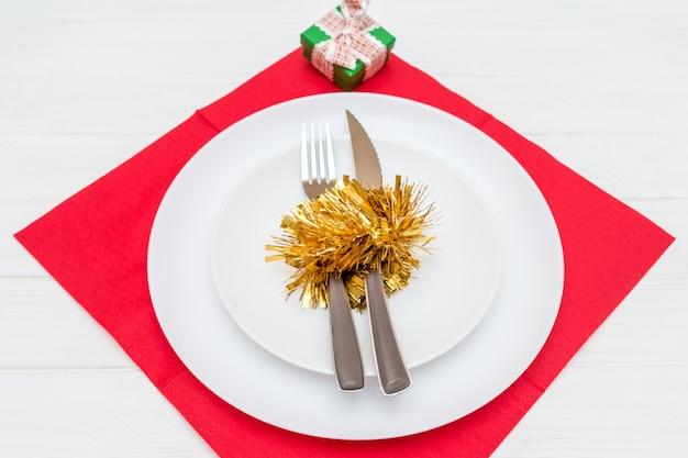 Нож и вилка в белой тарелке на красной салфетке, украшенной рождественским венком