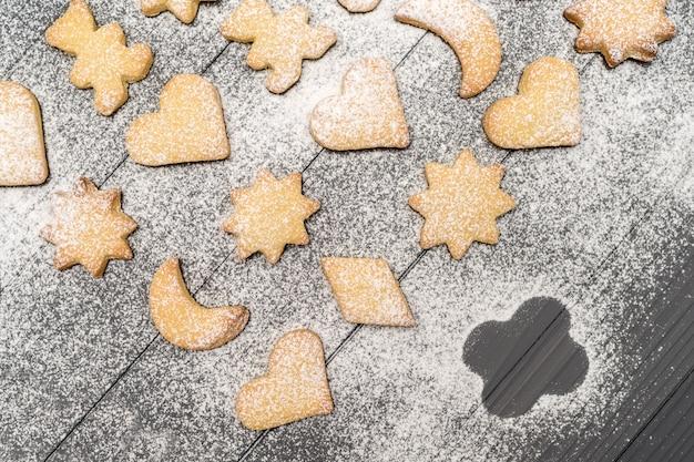 クリスマスの別の形の木製テーブルの上の砂糖の粉とクッキー