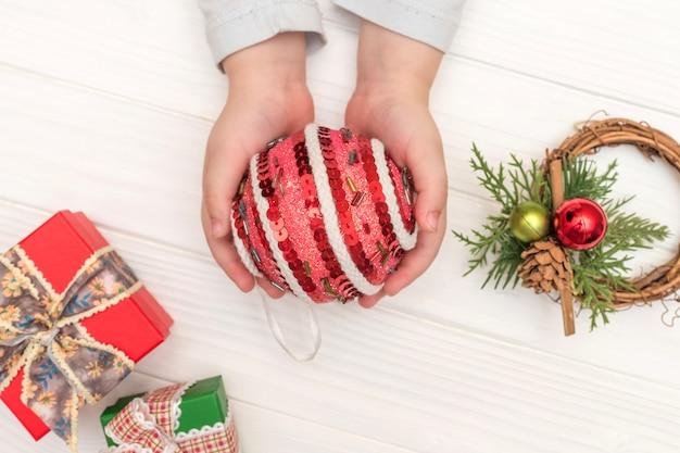 白い表面のクリスマスカレンダー。白いテーブルの上のギフトボックスの近くのクリスマスボールを保持している子供の手