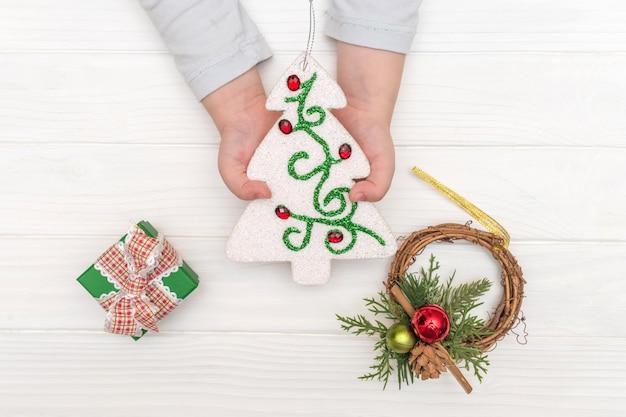 白い表面のクリスマスカレンダー。白いテーブルの上のギフトボックスの近くの装飾用のクリスマスツリーを保持している子供の手