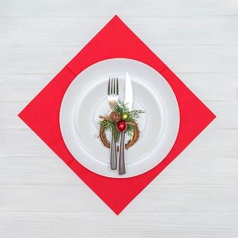 クリスマスリースで飾られた赤いナプキンに白い皿にナイフとフォーク