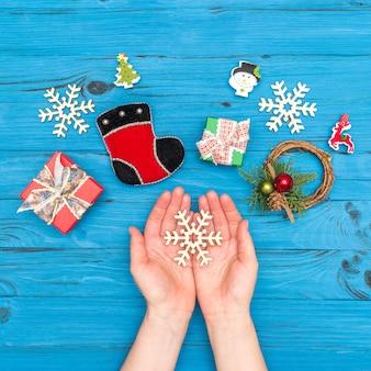 白い表面のクリスマスカレンダー。青い古いテーブルのギフトボックスと正月飾りの近くのクリスマス木製雪片を保持している女性の手