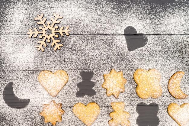 砂糖の粉と木製のテーブルに木製のスノーフレーククリスマスの異なる形のクッキー
