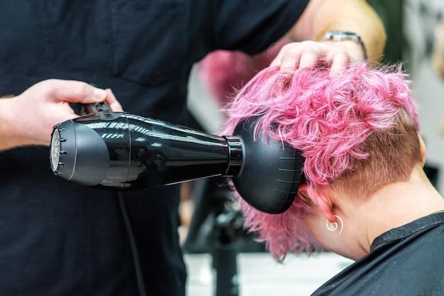 美容師はドライヤーで髪を乾かします