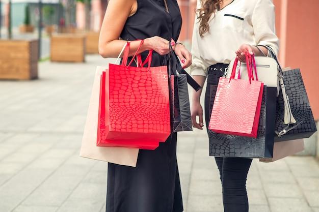 Две молодые девушки после покупок с сумками в руках.