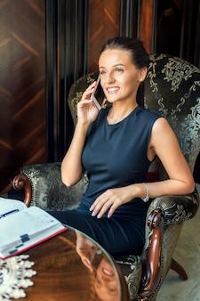 自宅でスマートフォンで話している笑顔の若い女性の肖像画。