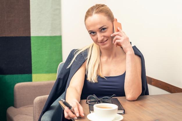 カフェでスマートフォンで話している成功した若い実業家。