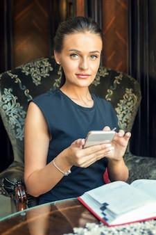 美しい若い実業家の肖像画は自宅でスマートフォンを使用しています。