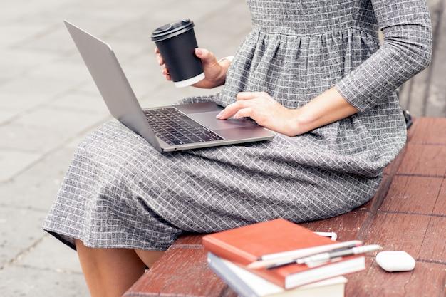 Студентка использует ноутбук, держа бумажный стаканчик сидит на скамейке.