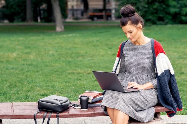 Студент девушка учится на ноутбуке в парке.