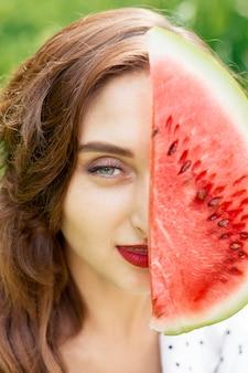 Крупным планом красивая девушка держит кусок арбуза, который покрывает часть ее лица.