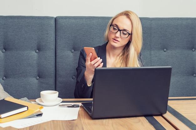 ビジネスの女性は、職場でスマートフォンを探しています