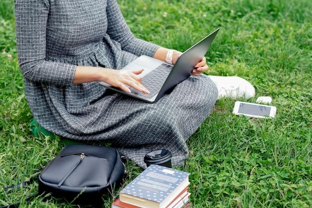 女子学生は屋外の芝生に座ってノートパソコンを使用しています。