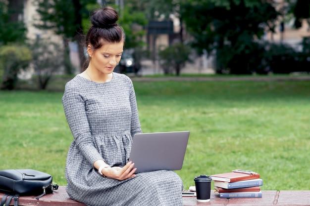 Студентка кавказской использует ноутбук на скамейке в парке.