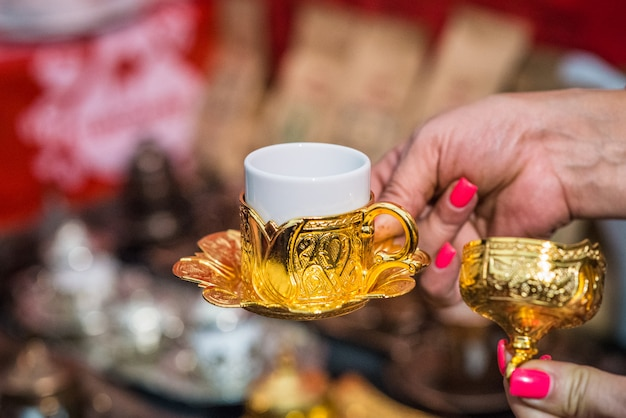 Рука держит чашку турецкого кофе