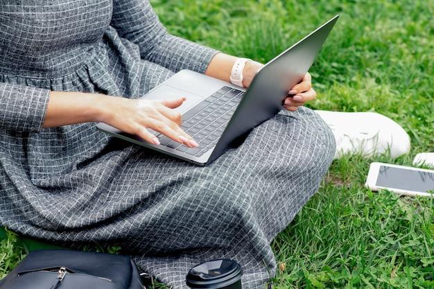 草の上に座っている間ノートパソコンを使用しての女子学生