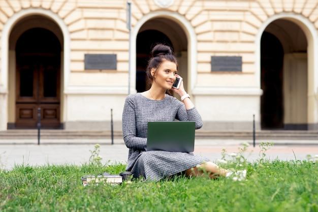 電話で話している学生の若い女性