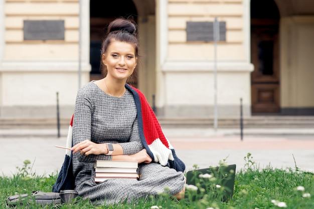 Студентка с книгами сидит на траве возле здания университета